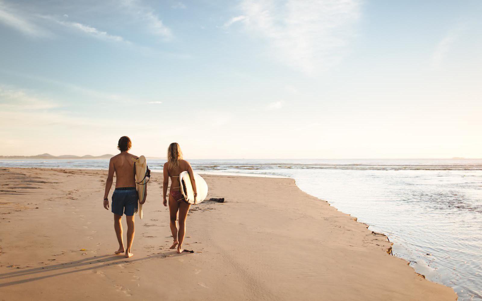 pärchen am strand spazieren im Sonnenuntergang